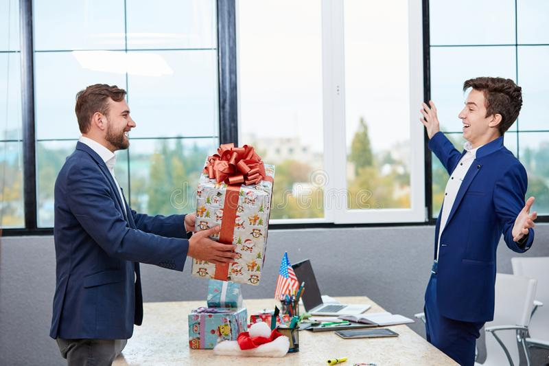 Portrait of joyful colleagues giving xmas presents to each other. Holiday concept. stock photography