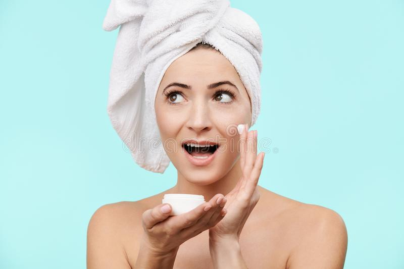 Attractive mid 30s woman applying moisturizer cream on her face. Photo of attractive caucasian woman with healthy skin. stock photography