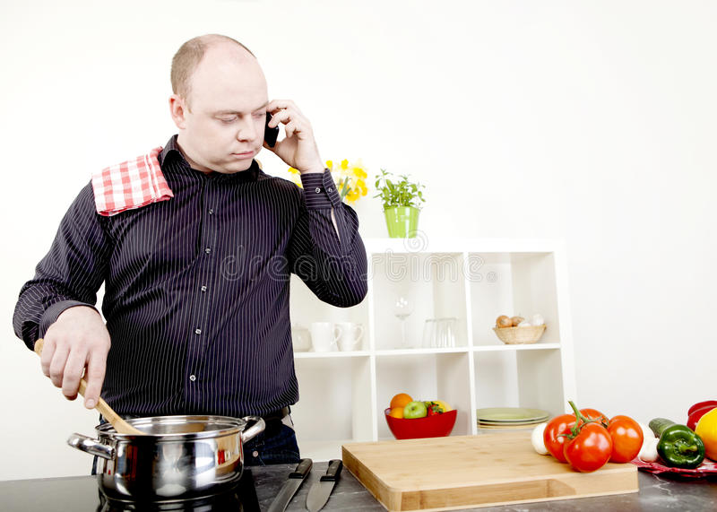 Man taking a call on his mobile while cooking royalty free stock photography