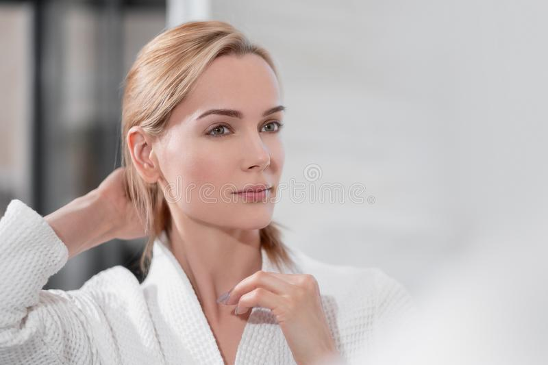 Attractive middle-aged blond woman in a white bathrobe stands in the bathroom by the mirror. She touches skin and smiles. Skin care concept stock photography
