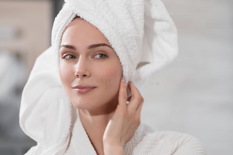 Attractive middle-aged blond woman with white towel on her head and in bathrobe standing in the bathroom by the mirror. She touches skin and smiles. Skin care stock photos