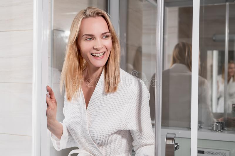 Attractive middle-aged blonde woman in a white bathrobe goes to the shower in the bathroom. Smiles and laughs. royalty free stock photography