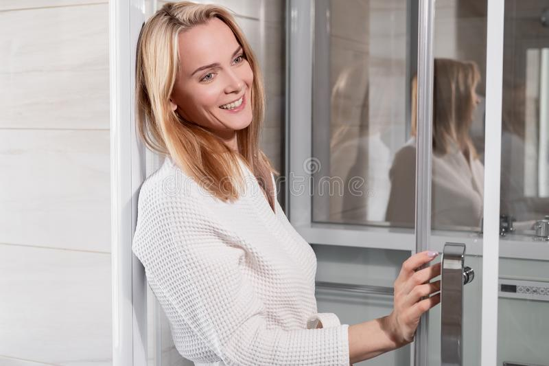 Attractive middle-aged blonde woman in a white bathrobe goes to the shower in the bathroom. Smiles and laughs. stock image
