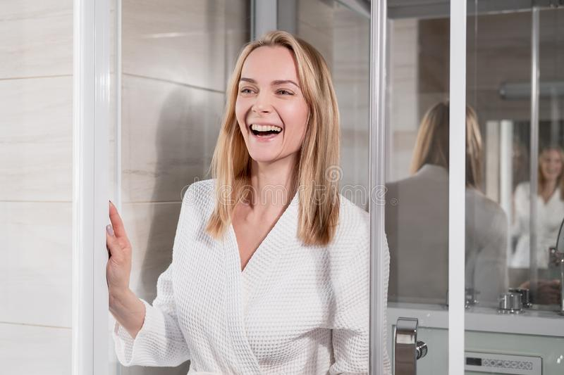 Attractive middle-aged blonde woman in a white bathrobe goes to the shower in the bathroom. Smiles and laughs. royalty free stock photo