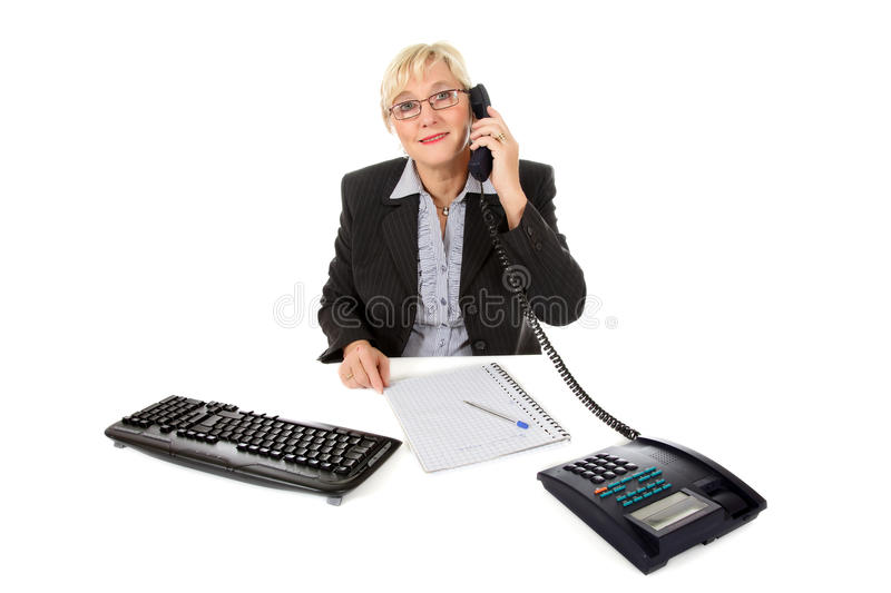 Attractive middle aged businesswoman at office. Attractive middle aged caucasian businesswoman in office talking by telephone, keyboard and notebook on her desk stock photography