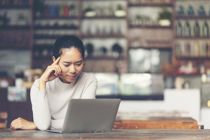 An attractive middle aged businesswoman sitting in front of laptop and managing her small business from home. stock images