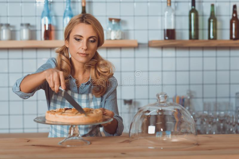 attractive middle aged cafe owner in apron cutting stock photo