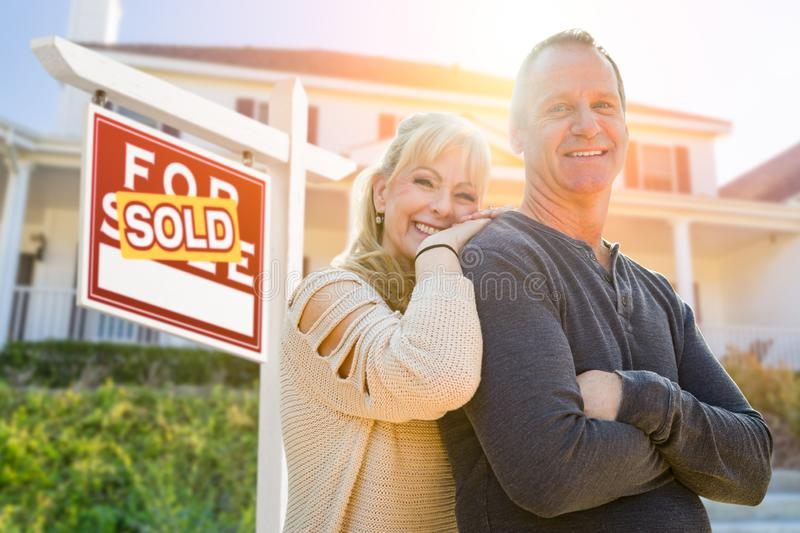 Attractive Middle-aged Couple In Front House and Sold Real Estate Sign.  royalty free stock photos