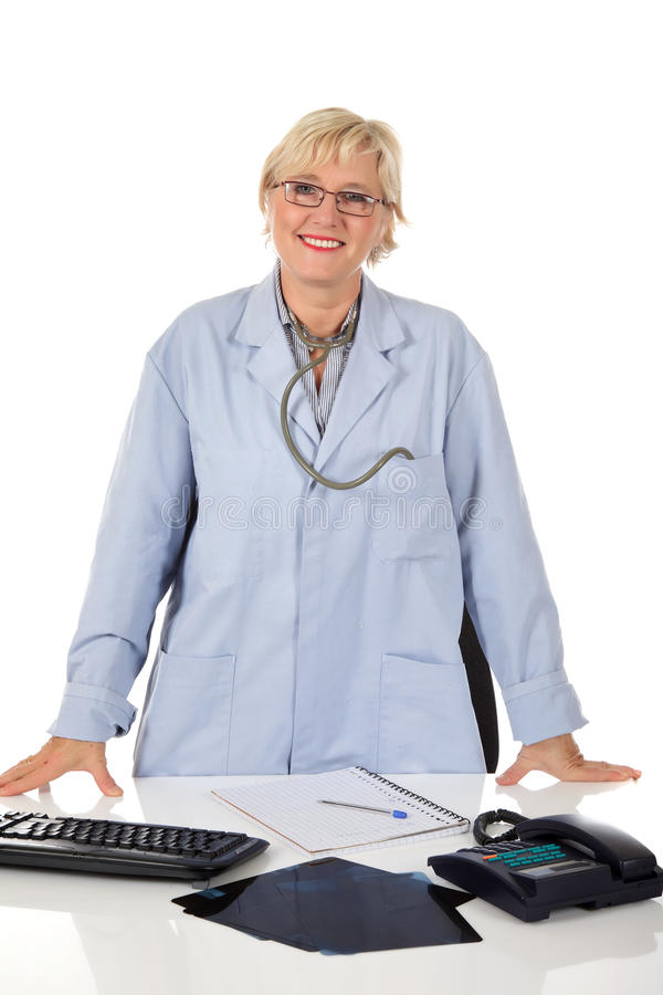 Attractive middle aged female doctor. In consulting room. X-ray photos, telephone and keyboard on her desk. Studio shot . White background royalty free stock photography