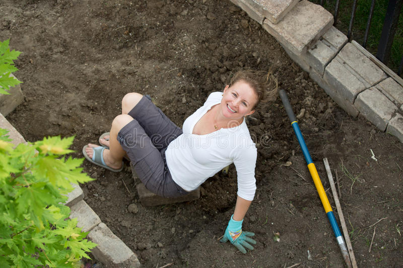 Attractive middle-aged female gardener. Working in her backyard doing maintenance on the flowerbeds, sitting on the newly dug over soil smiling up at the camera royalty free stock photos