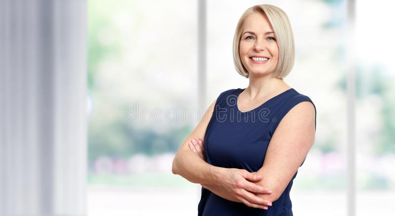 Attractive middle aged woman with a beautiful smile near the window. stock images