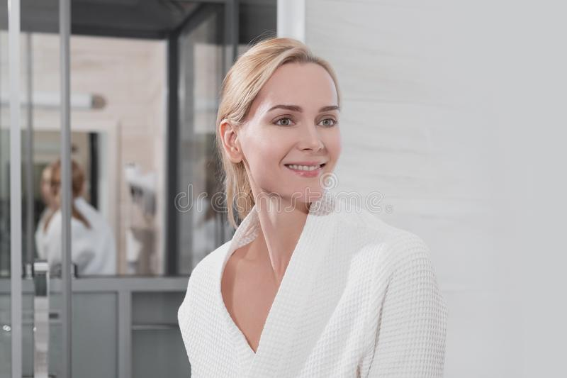 Attractive middle-aged woman a blonde in a white coat stands in the bathroom by the mirror. She touches skin and smiles. Beautiful white teeth lips and eyes royalty free stock photo