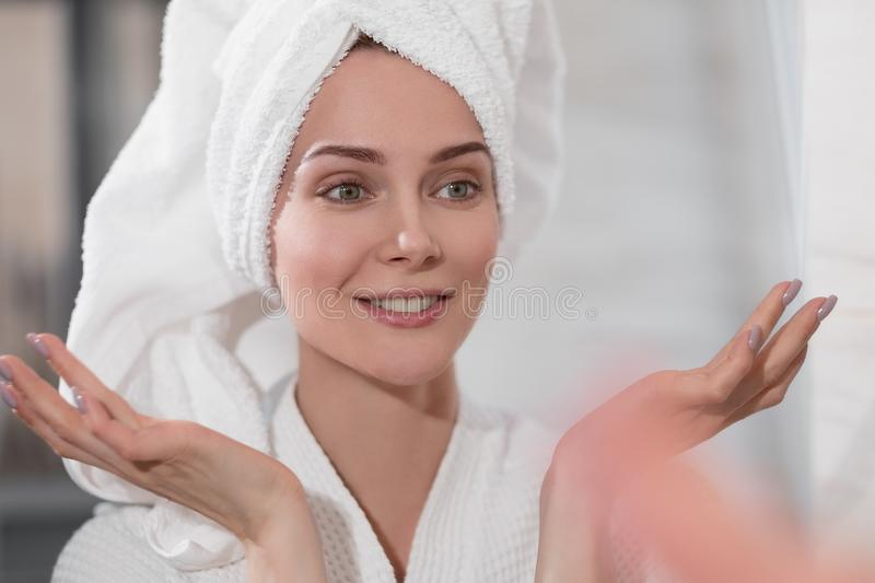 Attractive middle-aged woman a blonde with a white towel on her head and in a bathrobe is standing in the bathroom by. The mirror. He touches skin and smiles stock photo