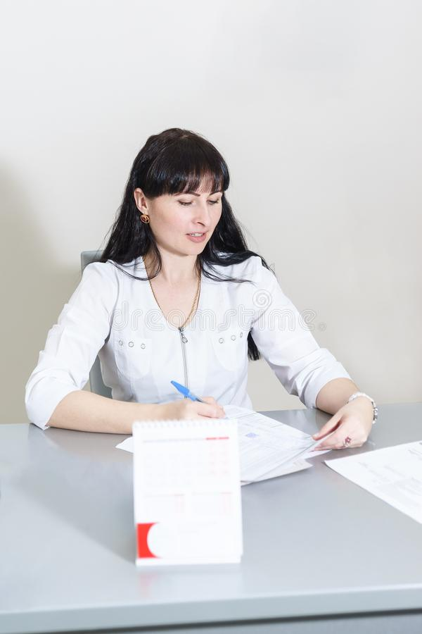 An attractive middle-aged woman doctor writes a prescription in an office at her Desk stock photography