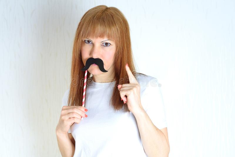 Attractive middle aged woman having fun with a fake moustache. stock photo