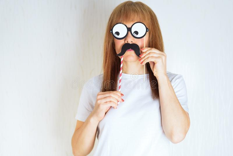 Attractive middle aged woman having fun with a fake moustache and glasses. royalty free stock photography