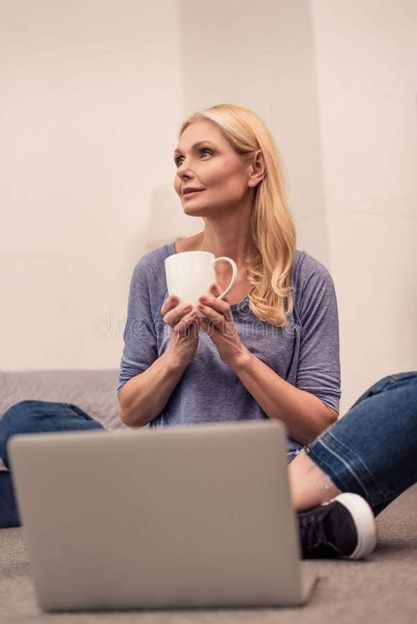 attractive middle aged woman holding cup of coffee while using laptop royalty free stock image