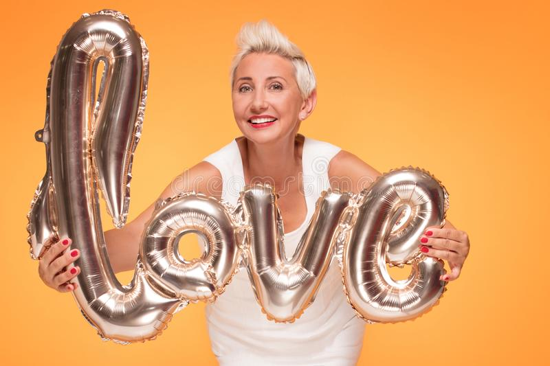 Attractive middle aged woman with love letters. Attractive middle aged woman holding gold love balloon, smiling to the camera. Yellow studio background stock photo