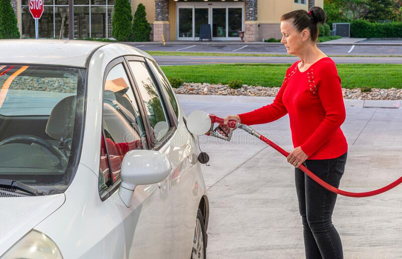 Attractive Middle-aged Woman Pumping Gasoline royalty free stock photos