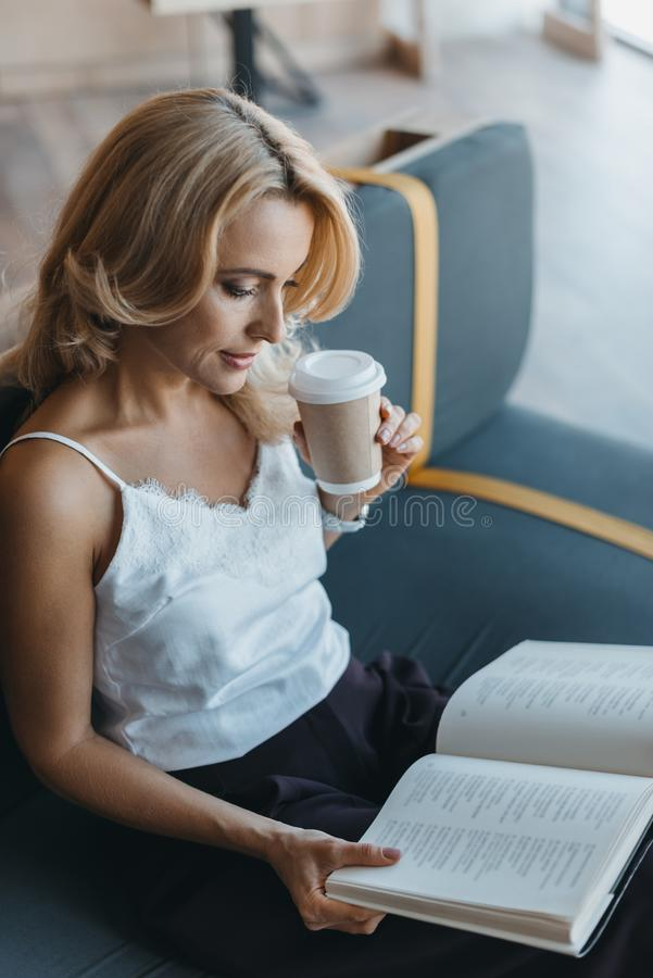 attractive middle aged woman reading book and drinking coffee stock photography