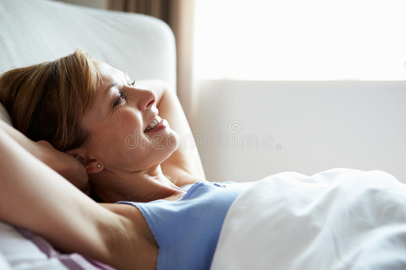 Attractive Middle Aged Woman Waking Up In Bed. Looking In Front Of Her Smiling royalty free stock photography