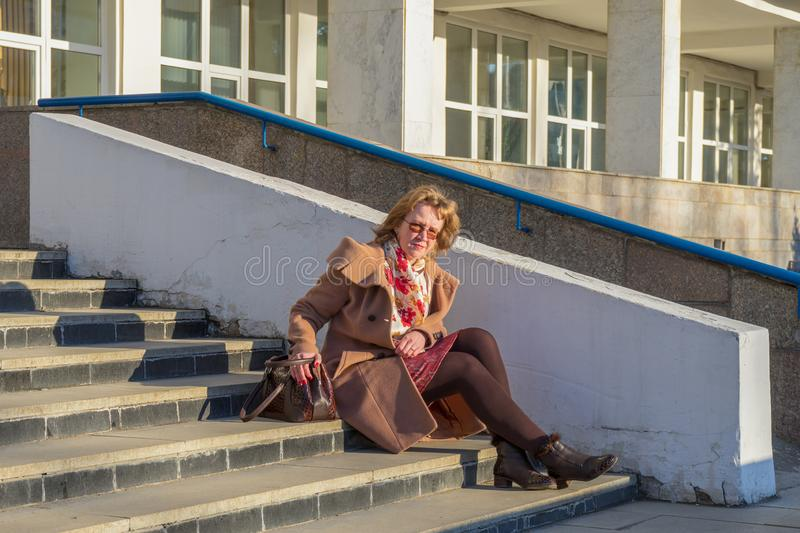 Attractive middle-aged woman wearing stylish coat and shoes sitting with bag on stairs step of office building in early spring at royalty free stock photos