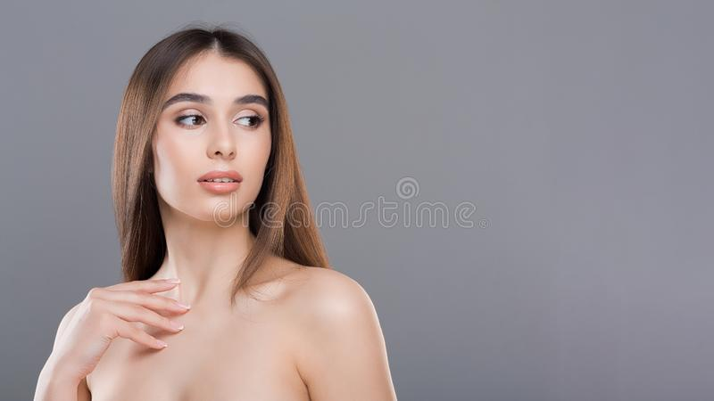 Attractive millennial nude woman with perfect skin. Pure beauty. Attractive millennial nude woman with perfect skin on grey panorama background, free space royalty free stock photography