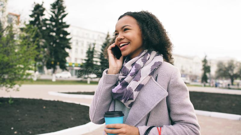 Attractive mixed race girl talking smartphone and drinking coffee walks in city street with bags. Young woman walking stock image