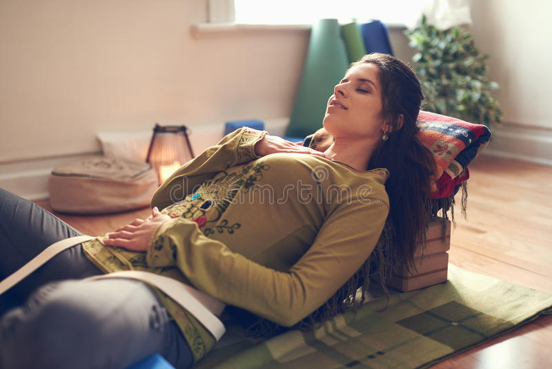 Attractive mixed race woman doing restorative yoga stock photo