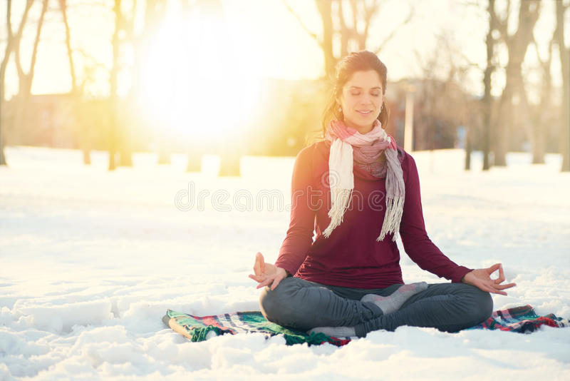 Attractive mixed race woman doing yoga in nature at winter time stock photos