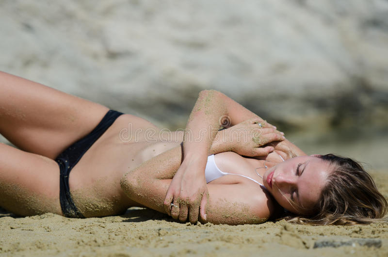 Attractive model with bikini on the sand in number of interesting poses royalty free stock photography