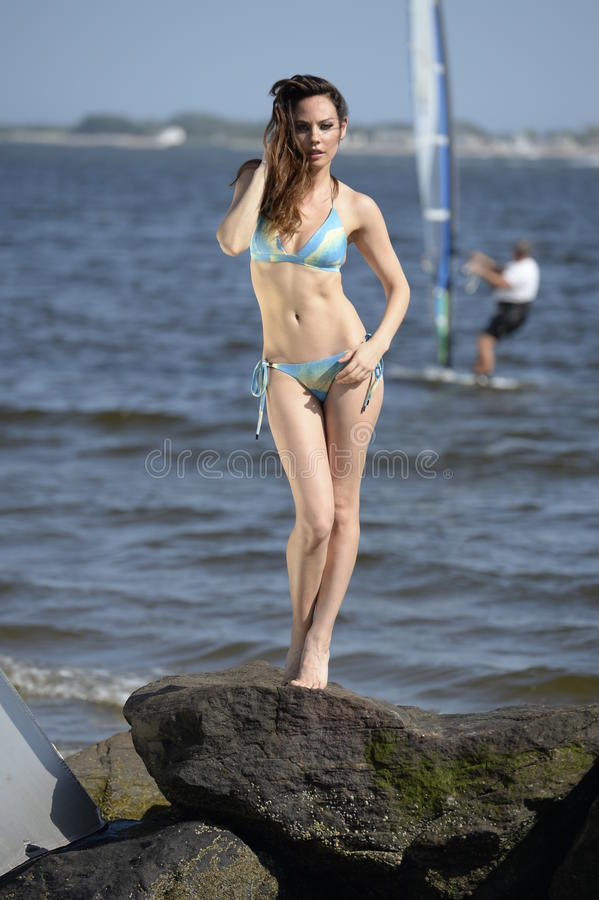Attractive model in blue bikini posing pretty at the beach rocks stock photography