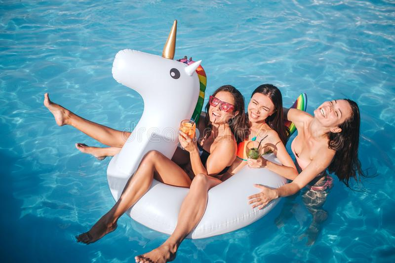 Attractive models are in swimming pool. They have cocktails in hands. Two models sit on float. Third one swimming behind stock photos
