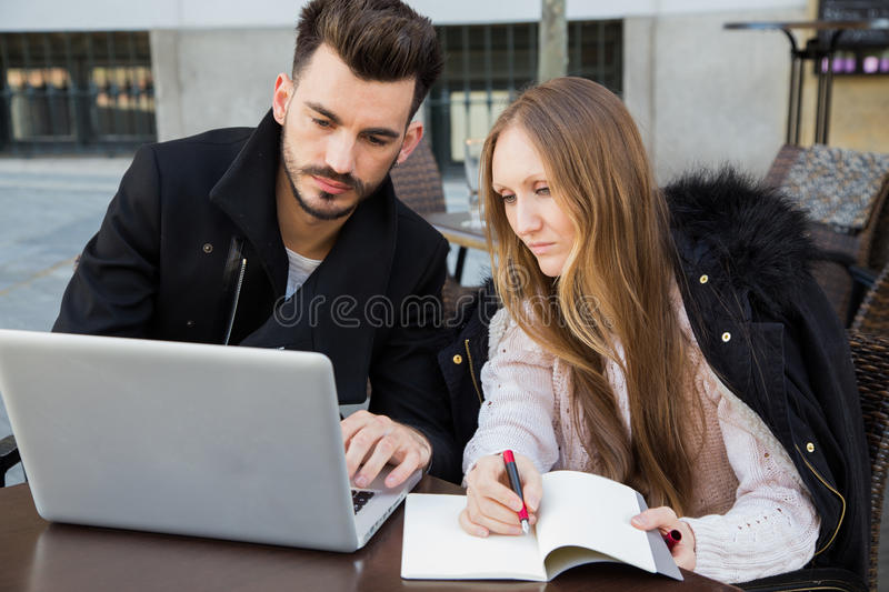 Attractive modern couple working on laptop outside. Attractive modern couple working on laptop in a terrace. Business team royalty free stock images