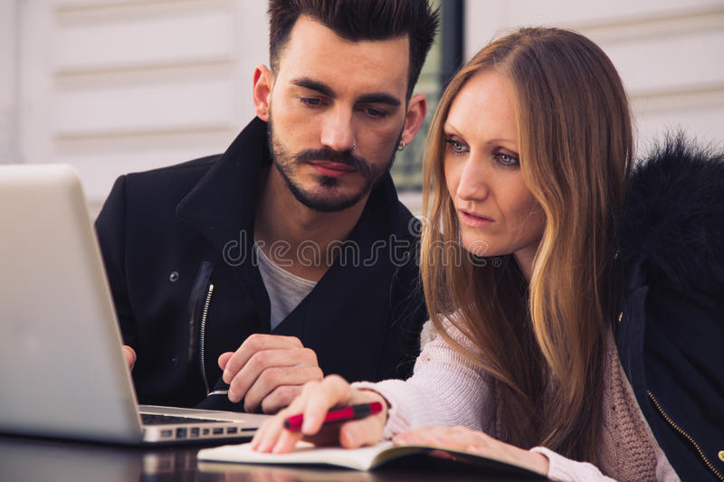 Attractive modern couple working on laptop outside. Attractive modern couple working on laptop in a terrace. Business team stock photography
