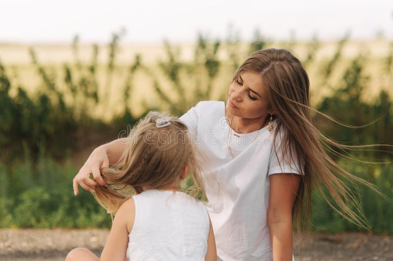 Attractive Mom and blonde hair daughter sits on road near big alley. They smile and look to natune.  royalty free stock images