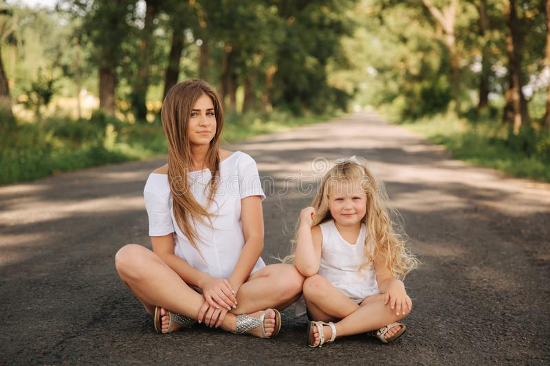 Attractive Mom and blonde hair daughter sits on road near big alley. They smile and look to natune. Front view.  royalty free stock images