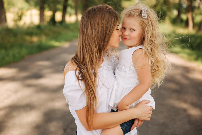 Attractive Mom and blonde hair daughter sits on road near big alley. They smile and look to natune. Front view.  stock photos