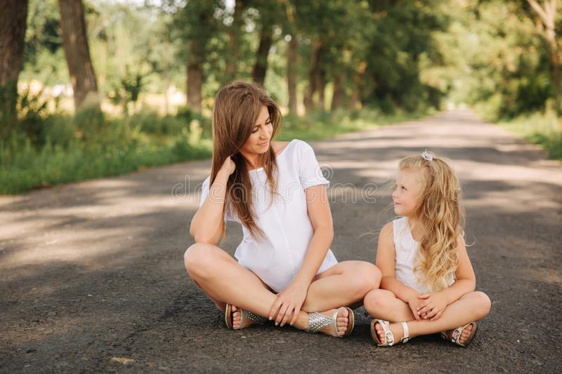 Attractive Mom and blonde hair daughter sits on road near big alley. They smile and look to natune. Front view.  royalty free stock photos