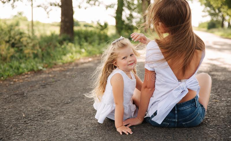 Attractive Mom and blonde hair daughter sits on road near big alley. They smile and look to natune. Back view. Attractive Mom and blonde hair daughter sits on stock photos