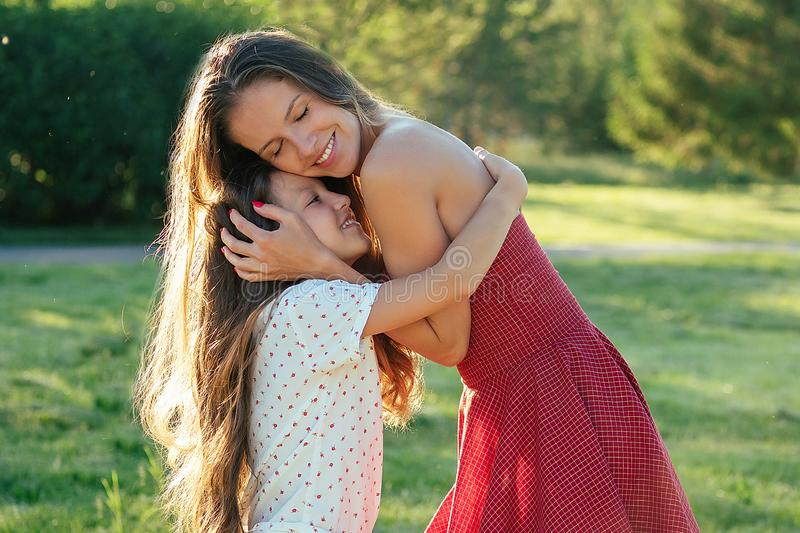 Attractive mother in a cocktail dress hugging her dear beautiful daughter long hair in the park summer trip. healthy royalty free stock images