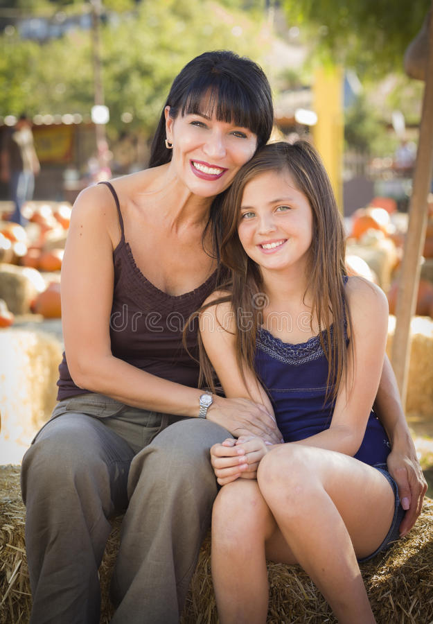 Attractive Mother and Daughter Portrait at the Pumpkin Patch stock photo