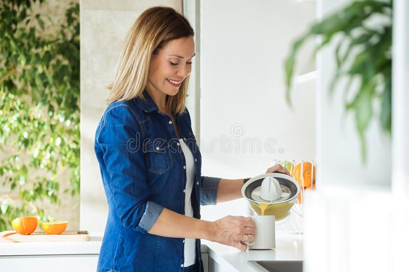 Attractive mother making a freshly squeezed orange juice with the help of a citrus juicer on a kitchen counter at home royalty free stock photo