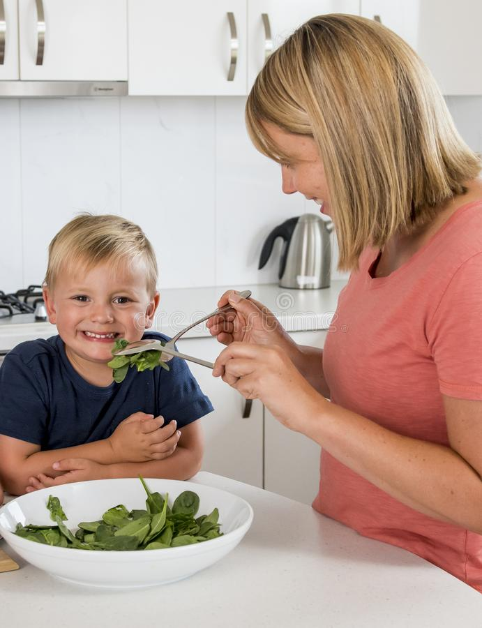 Attractive mother preparing salad together with little 3 year ol royalty free stock photography