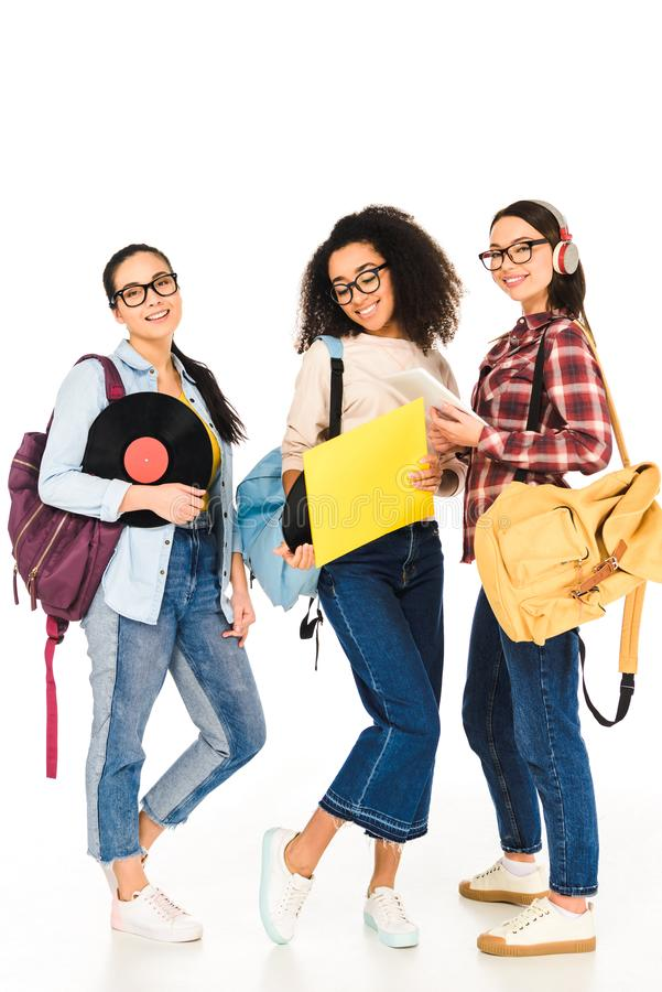 Attractive multicultural girls in glasses with vinyl records isolated. On white royalty free stock photos