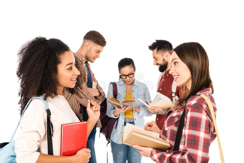 Attractive multiethnic girls talking with books in hands near group of young people isolated. On white stock photo