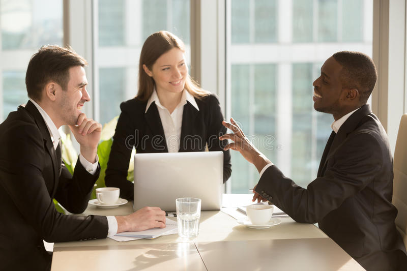 Attractive multiracial businesspeople talking and joking, having stock photo