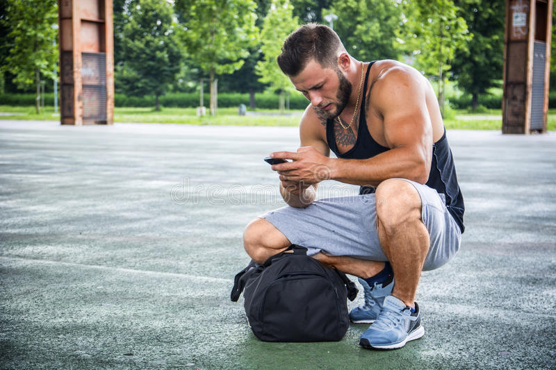 Attractive muscleman using cell phone in city park. Attractive muscleman using cell phone from his bag in city park, ready for training or jogging royalty free stock photos