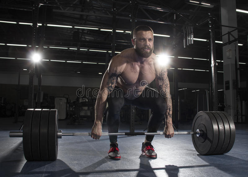 Attractive muscular bodybuilder doing deadlifts in modern gym.F royalty free stock photography