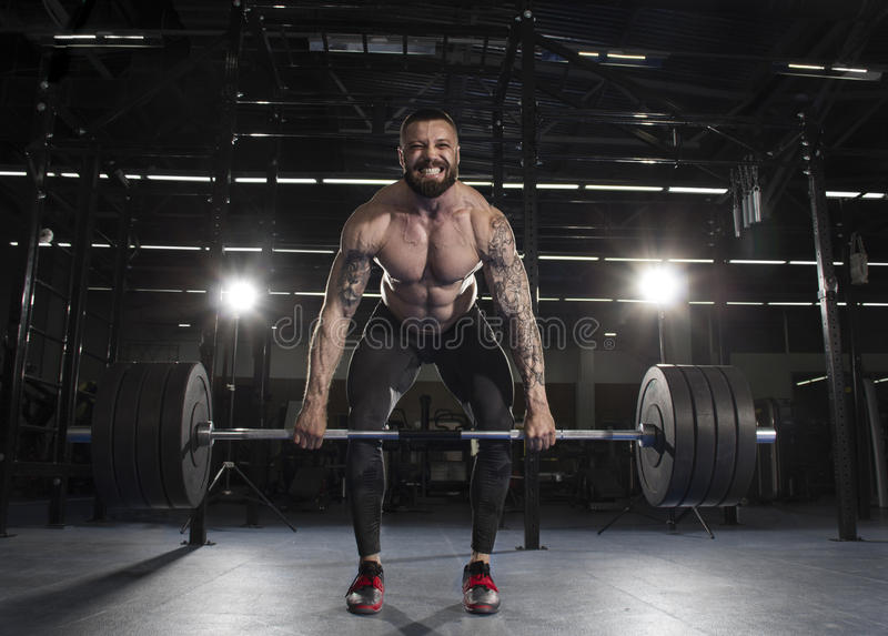 Attractive muscular bodybuilder doing heavy deadlift exercise in royalty free stock photography